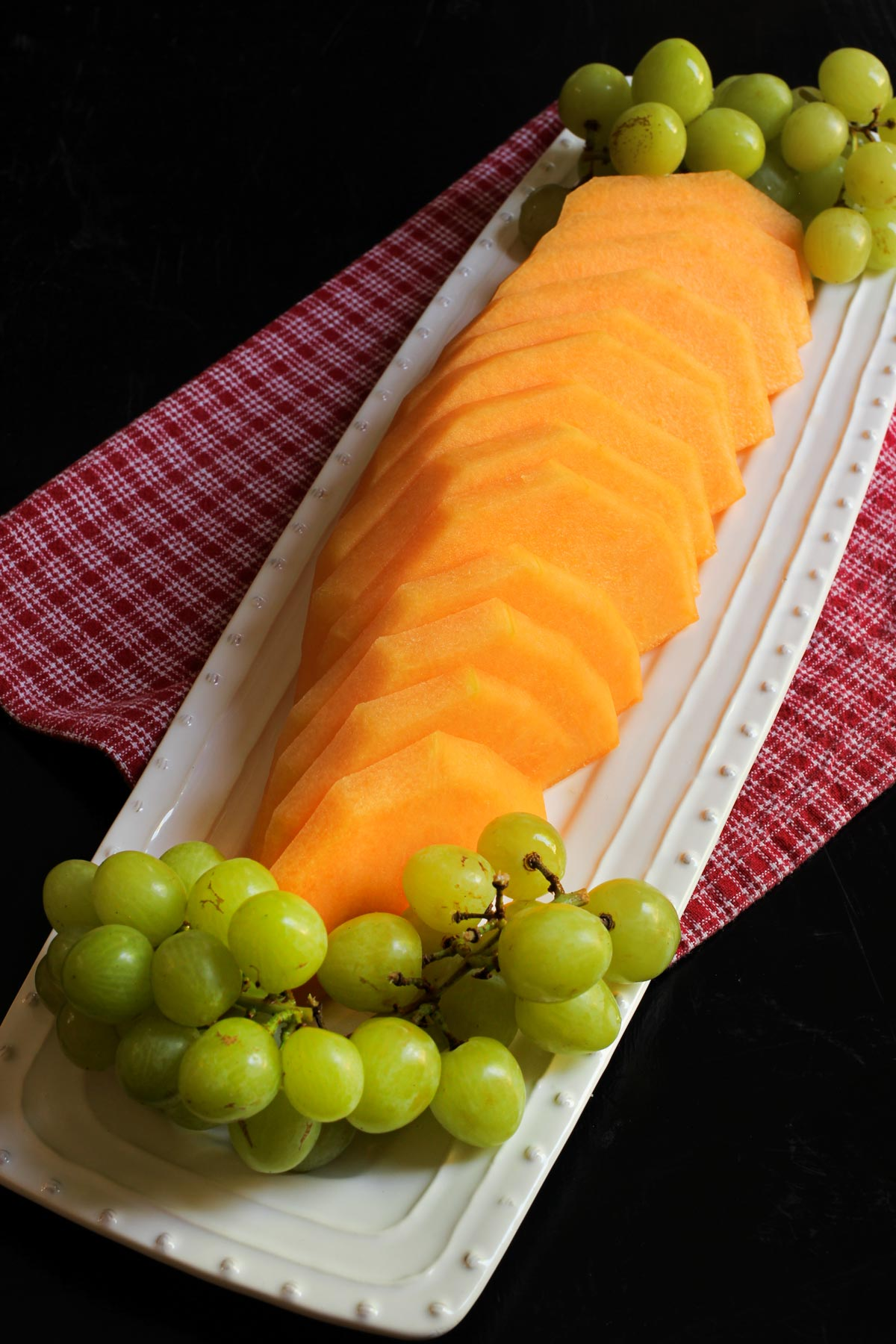 white platter of melon slices and green grape clusters.