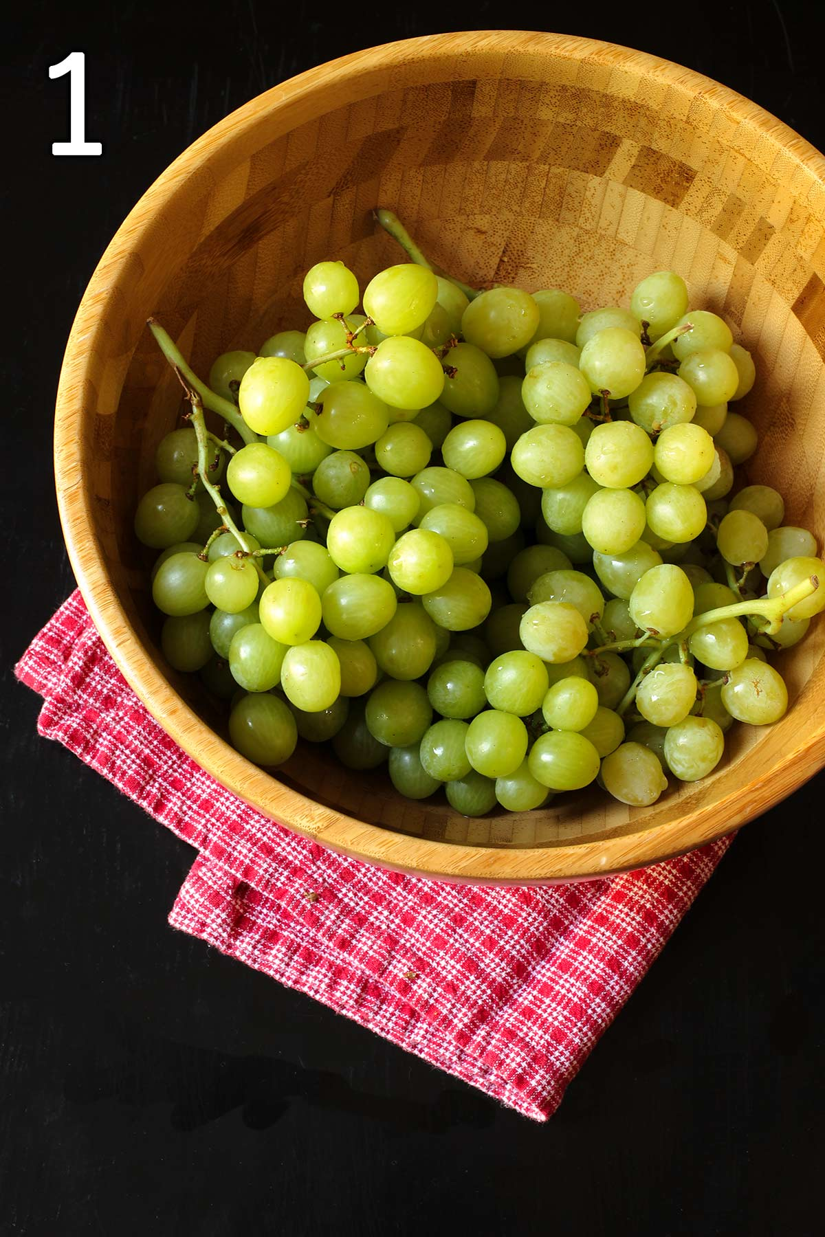 washed green grapes in a large wooden bowl on a red cloth.