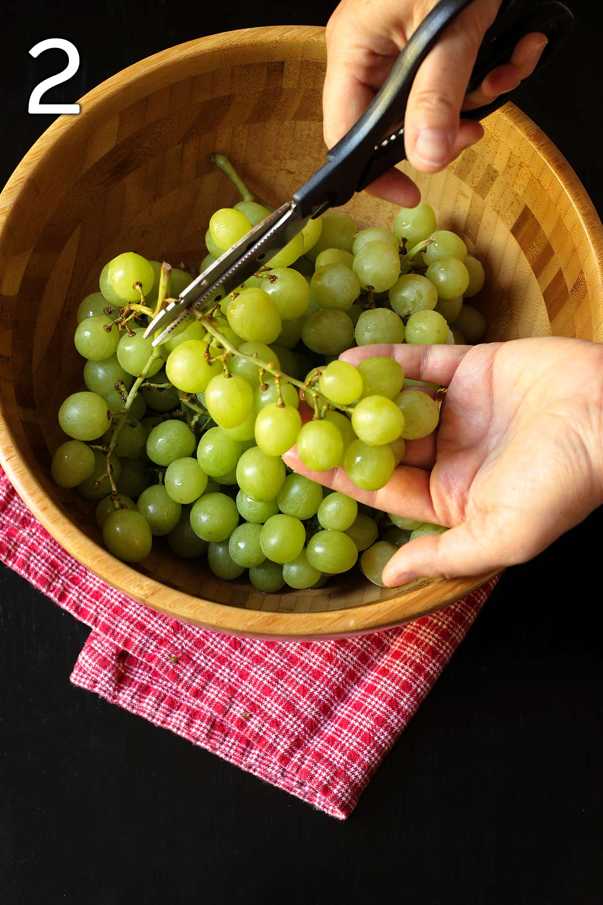 woman cutting off a cluster of grapes into the palm of her hand with kitchen shears.