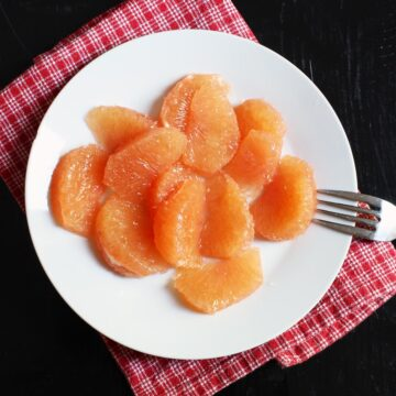 plate of grapefruit sections with fork.