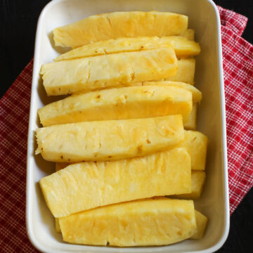 spears of cut pineapple lined up in ceramic dish.