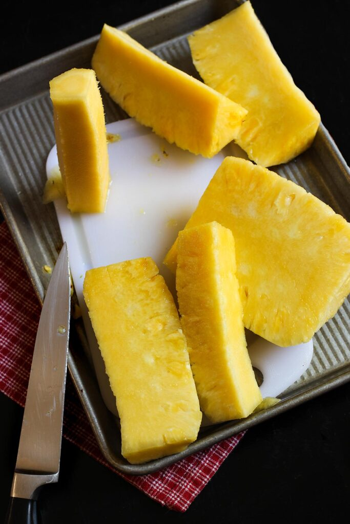 chunks of pineapple on the cutting board with the core standing out on the board.