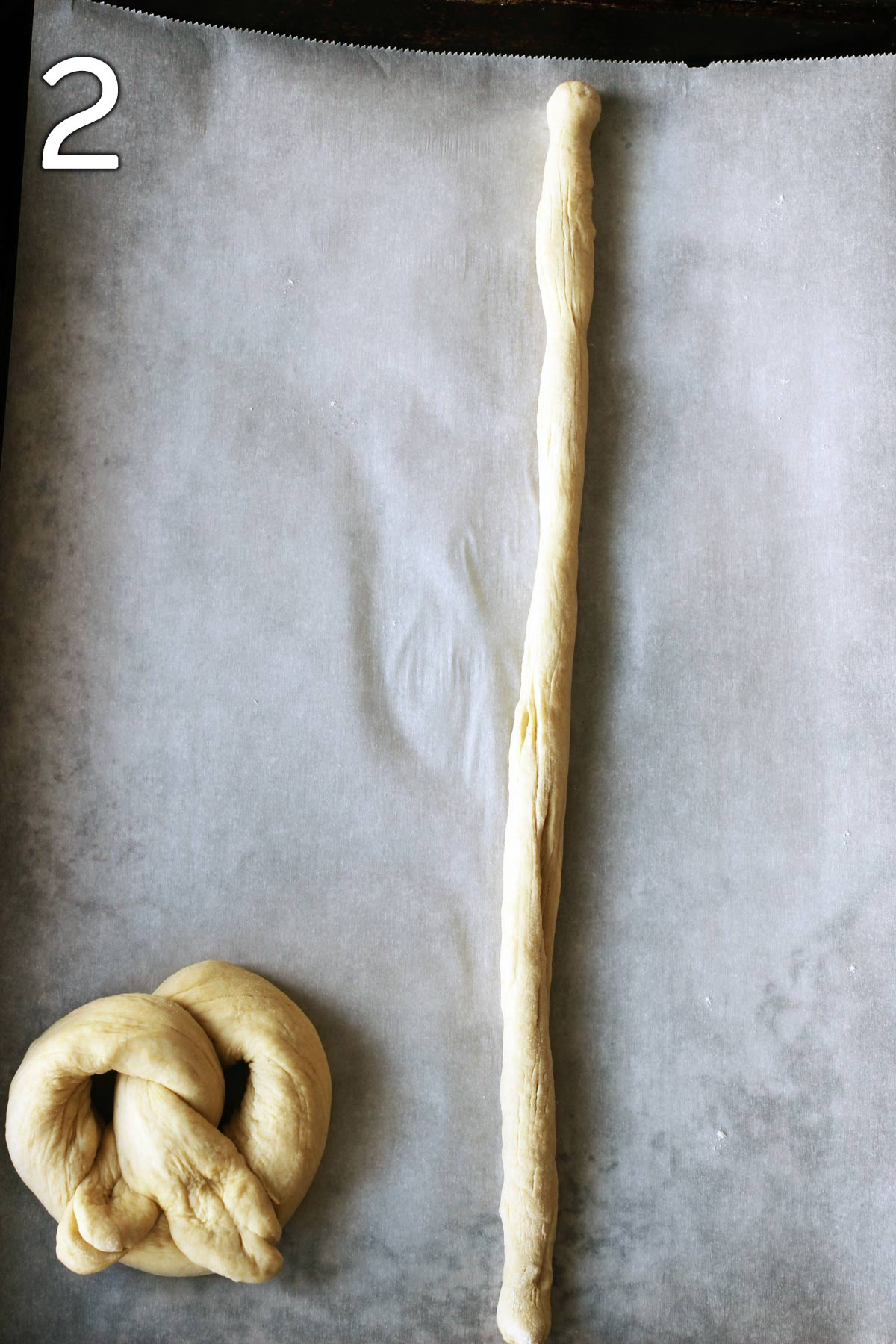 formed pretzel on tray next to long dough snake.