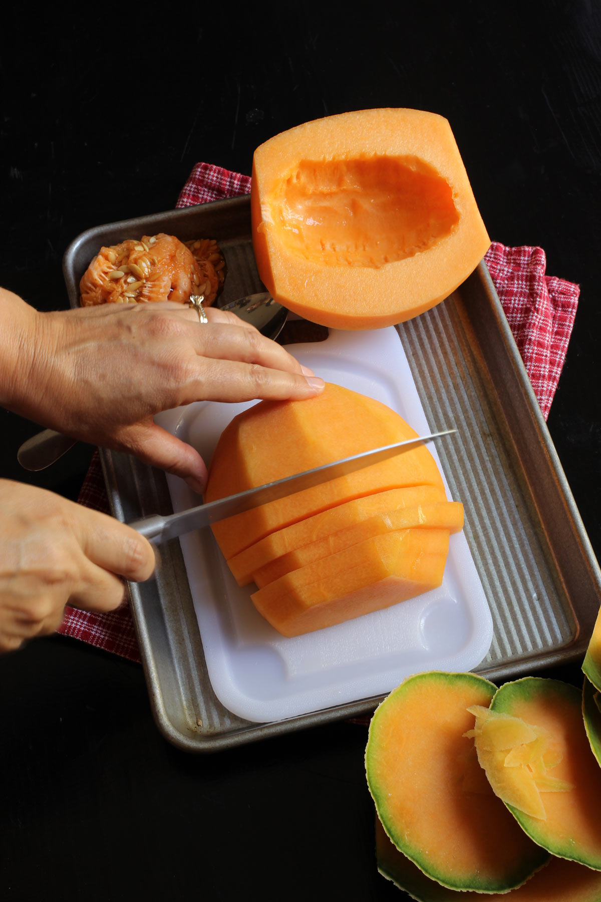 cutting cantaloupe half into slices on cutting board.