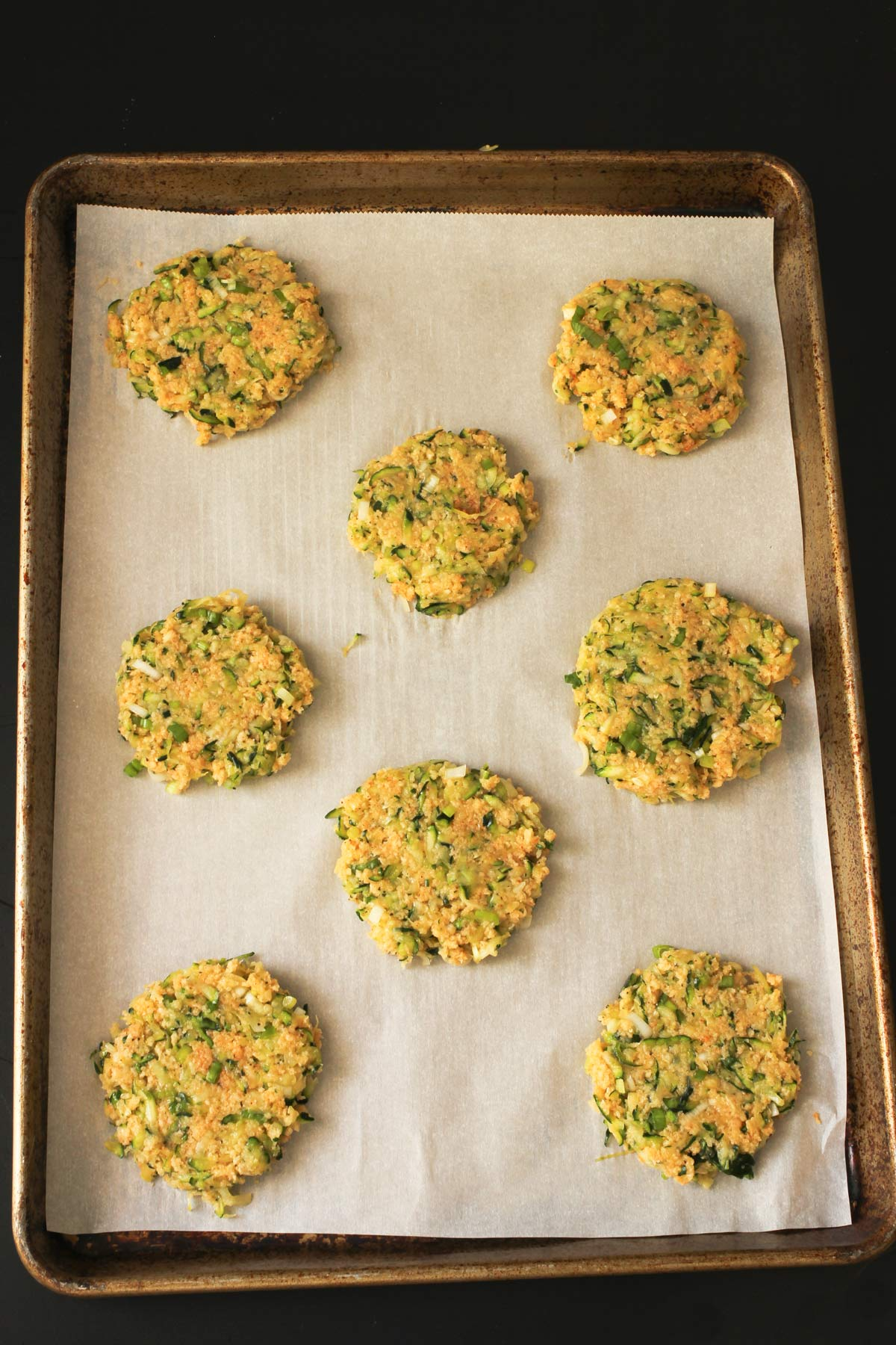 zucchini fritters on lined tray ready for baking.