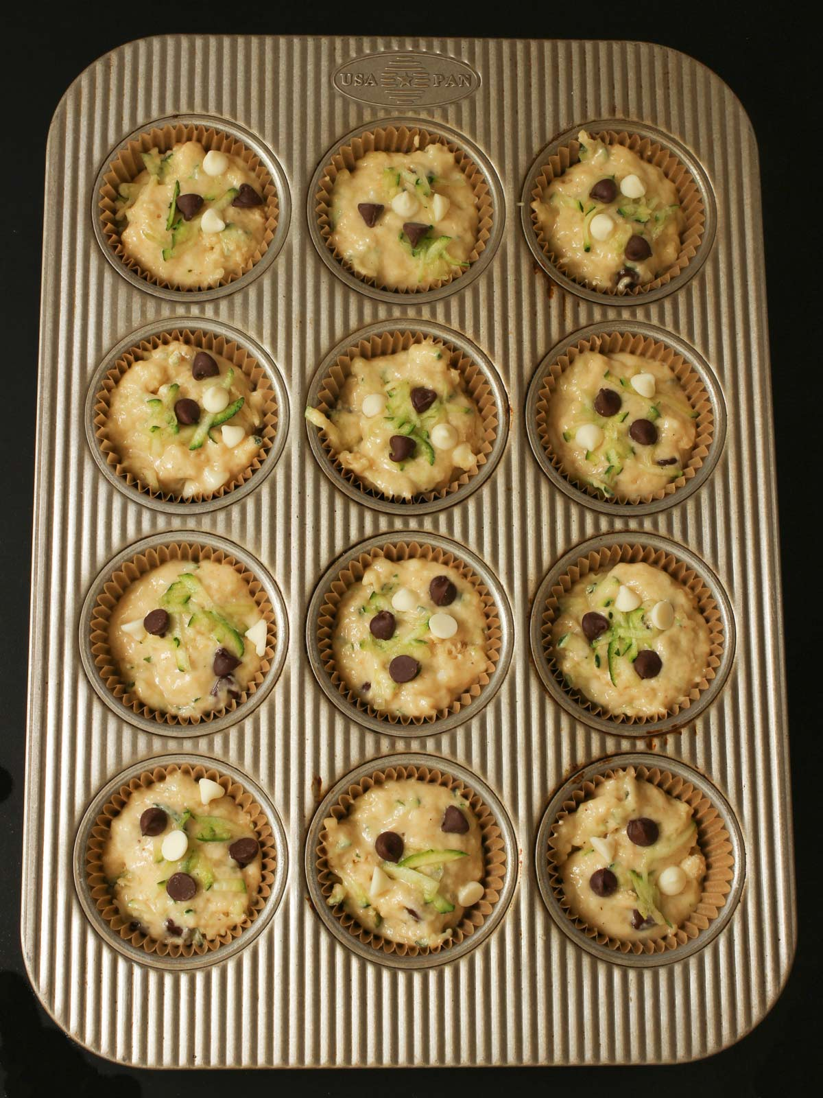 chocolate chips topping the uncooked batter in the muffin tins.