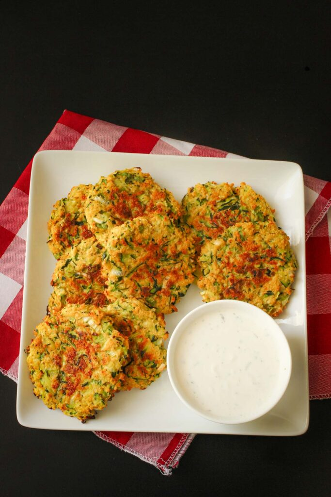 baked zucchini fritters on square white platter with dipping bowl of ranch.