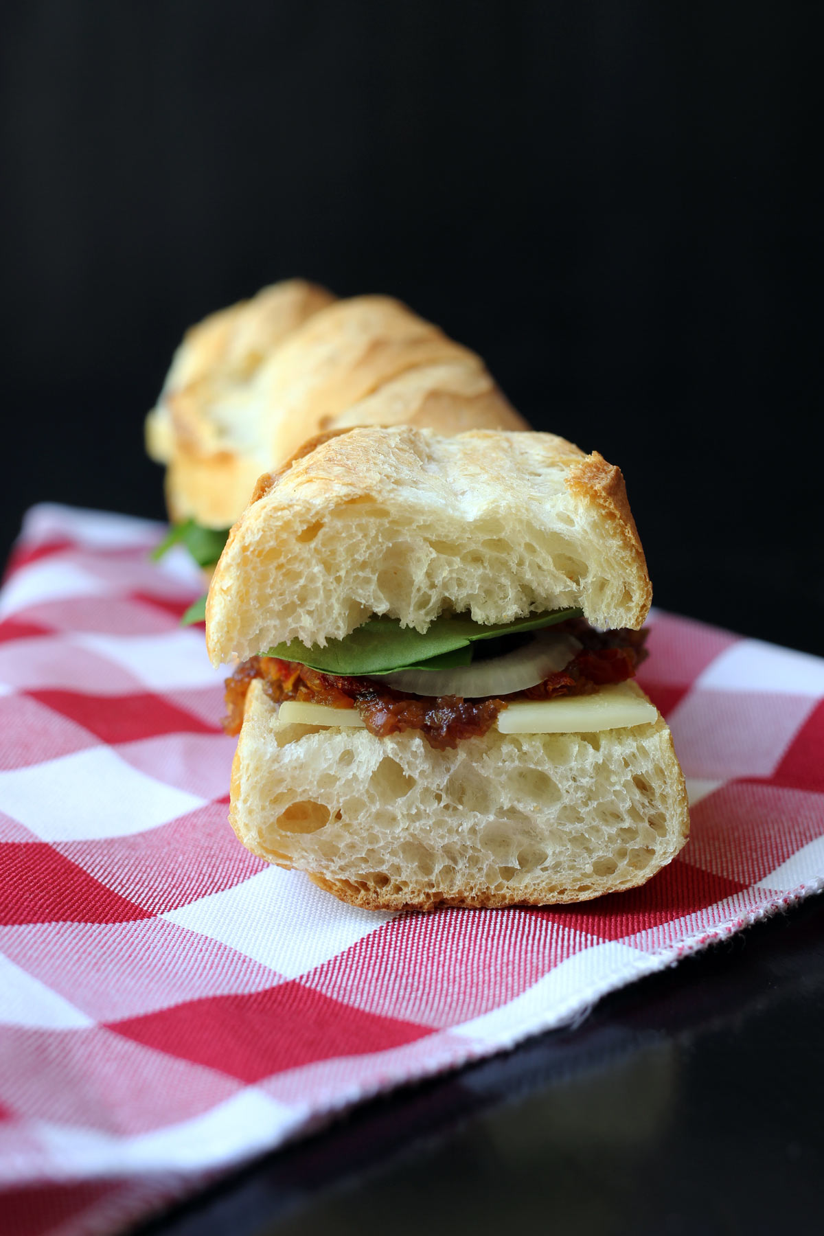 baguette sandwich with open end facing to show laters of cheese, English pickle, onion, and spinach.