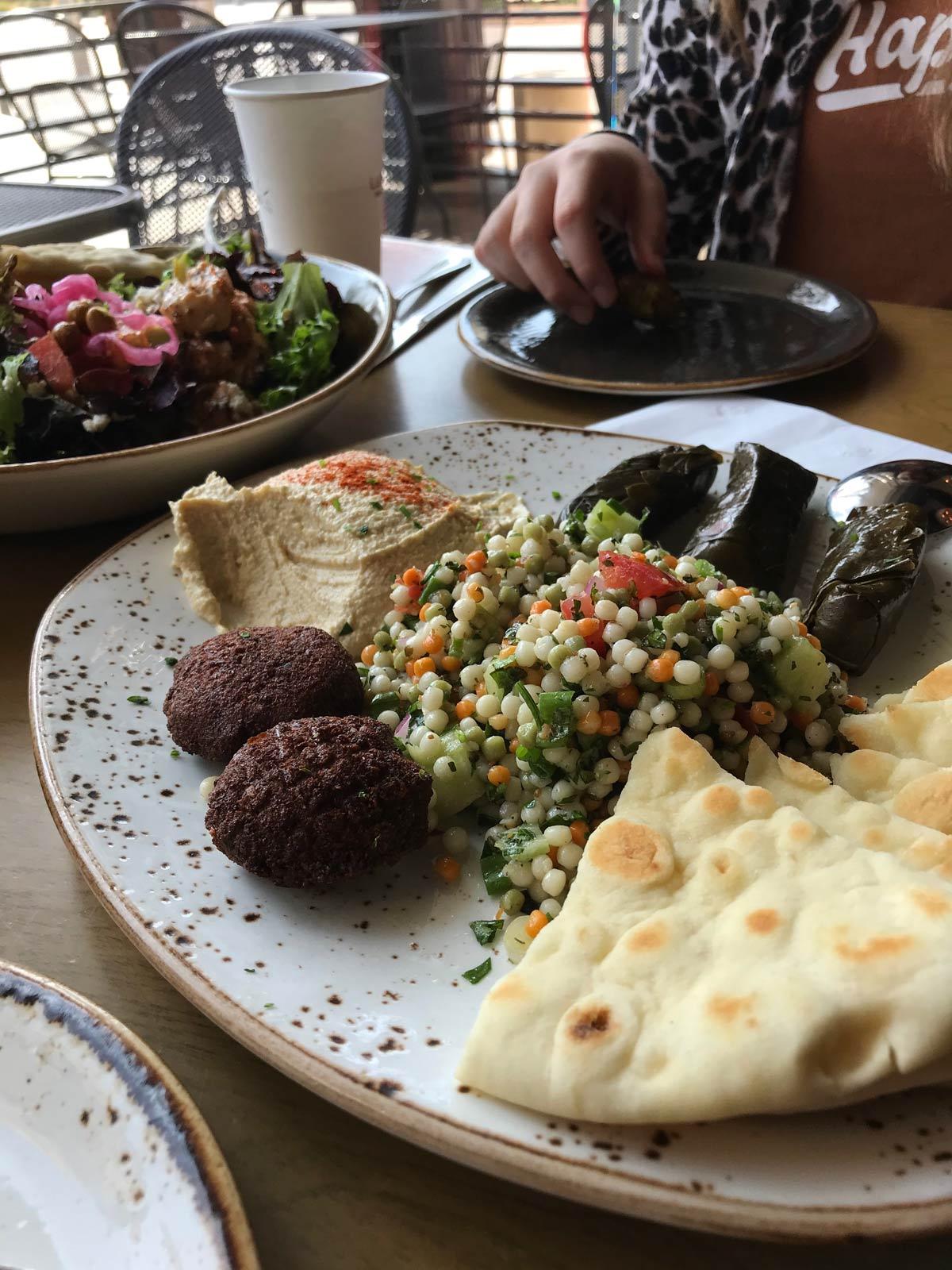 sampler appetizer platter at Luna Grill with salad in background.