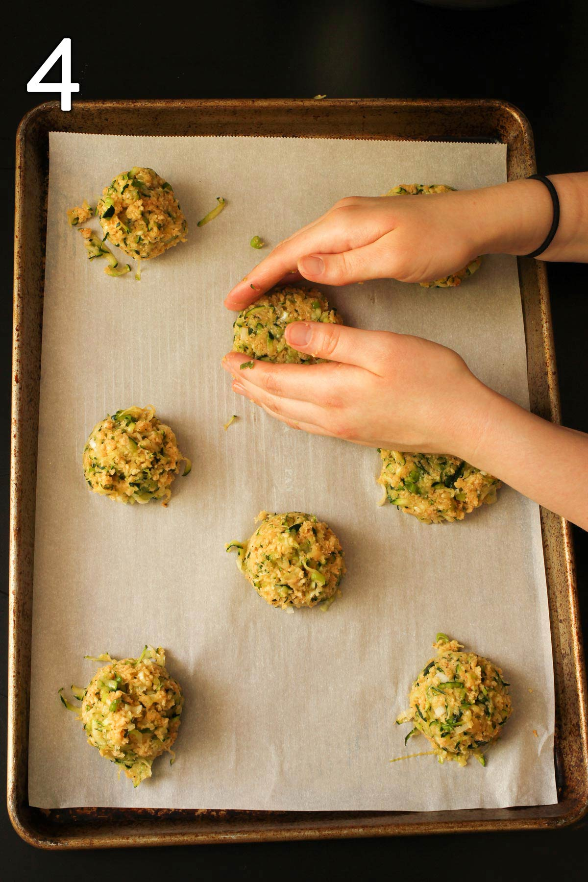 hands forming scoops of zucchini mixture into patties