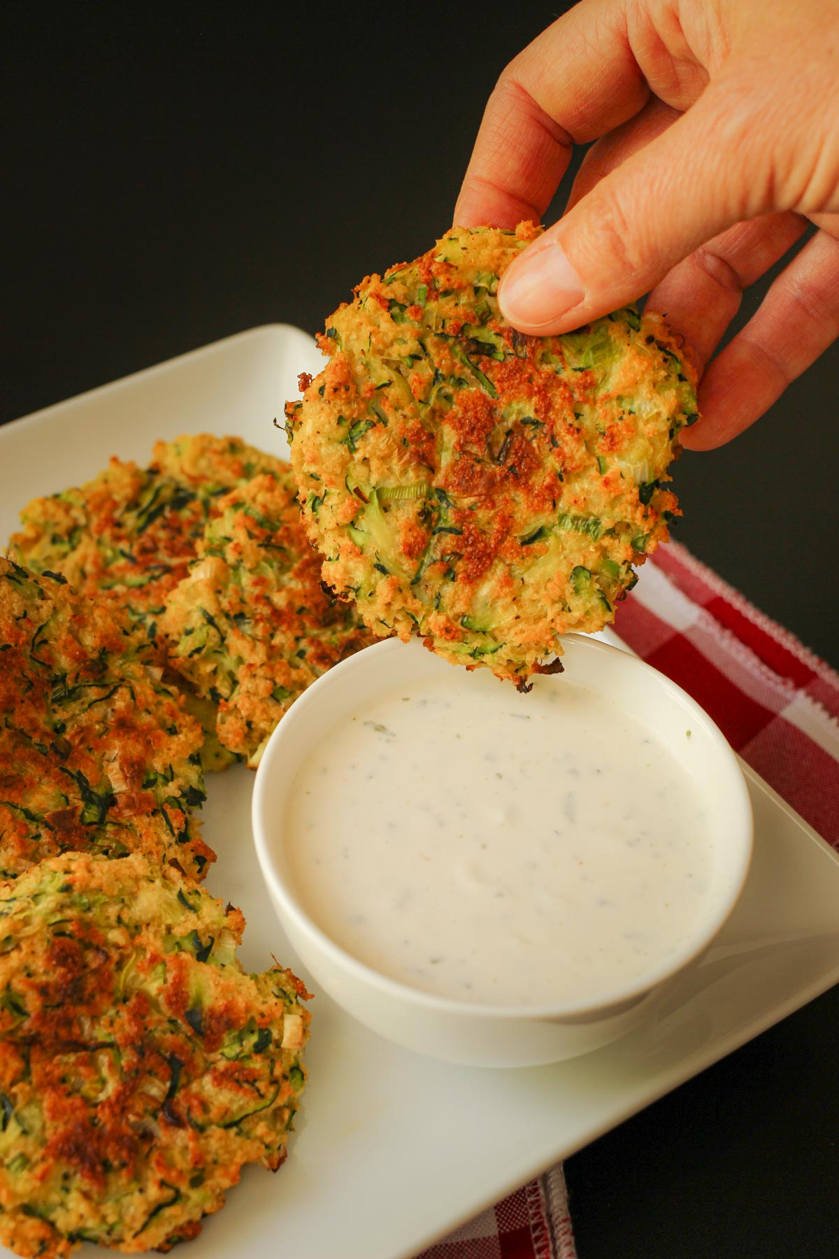 dipping a baked zucchini fritter into a small bowl of ranch dip.