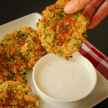 hand dipping a baked zucchini fritter into a small white dish of ranch.