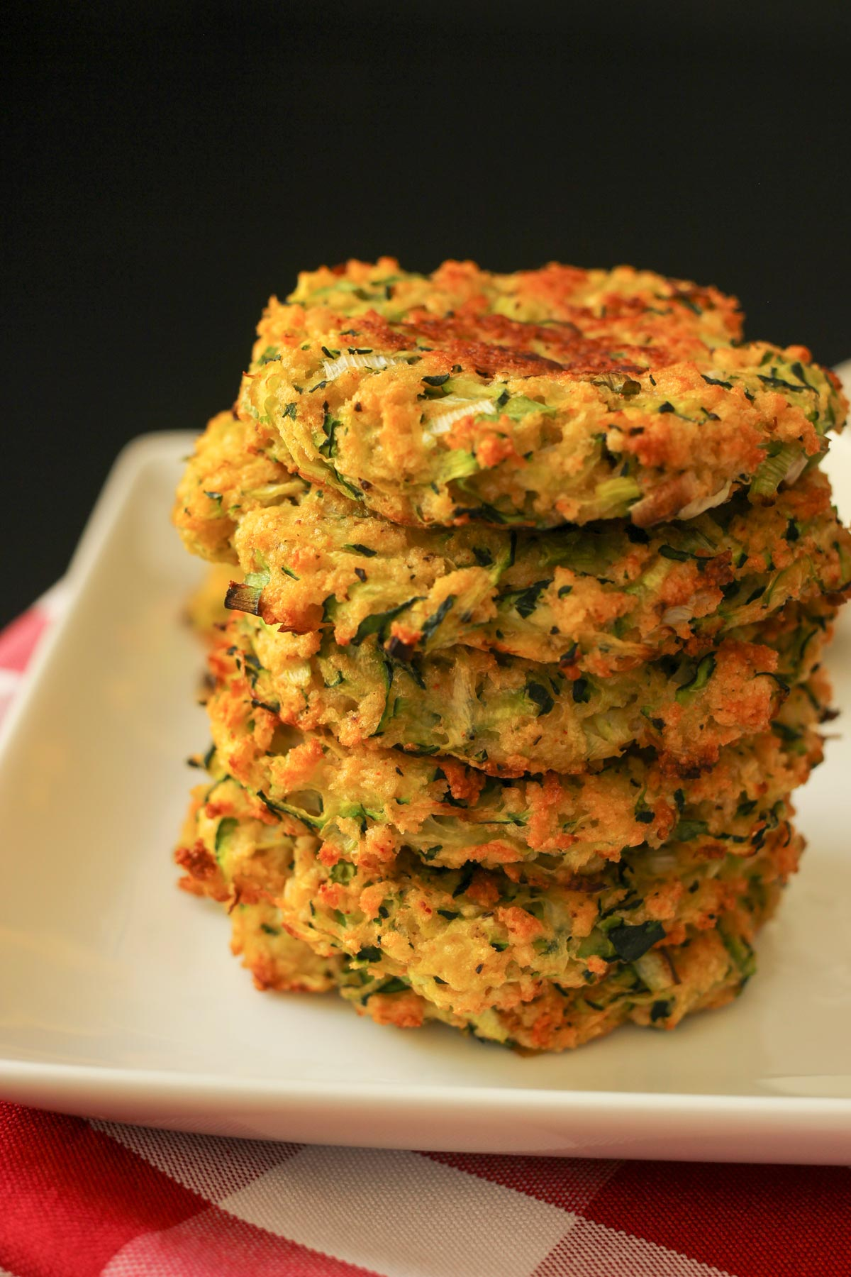 stack of baked zucchini fritters on a white square plate on red-checked napkin.