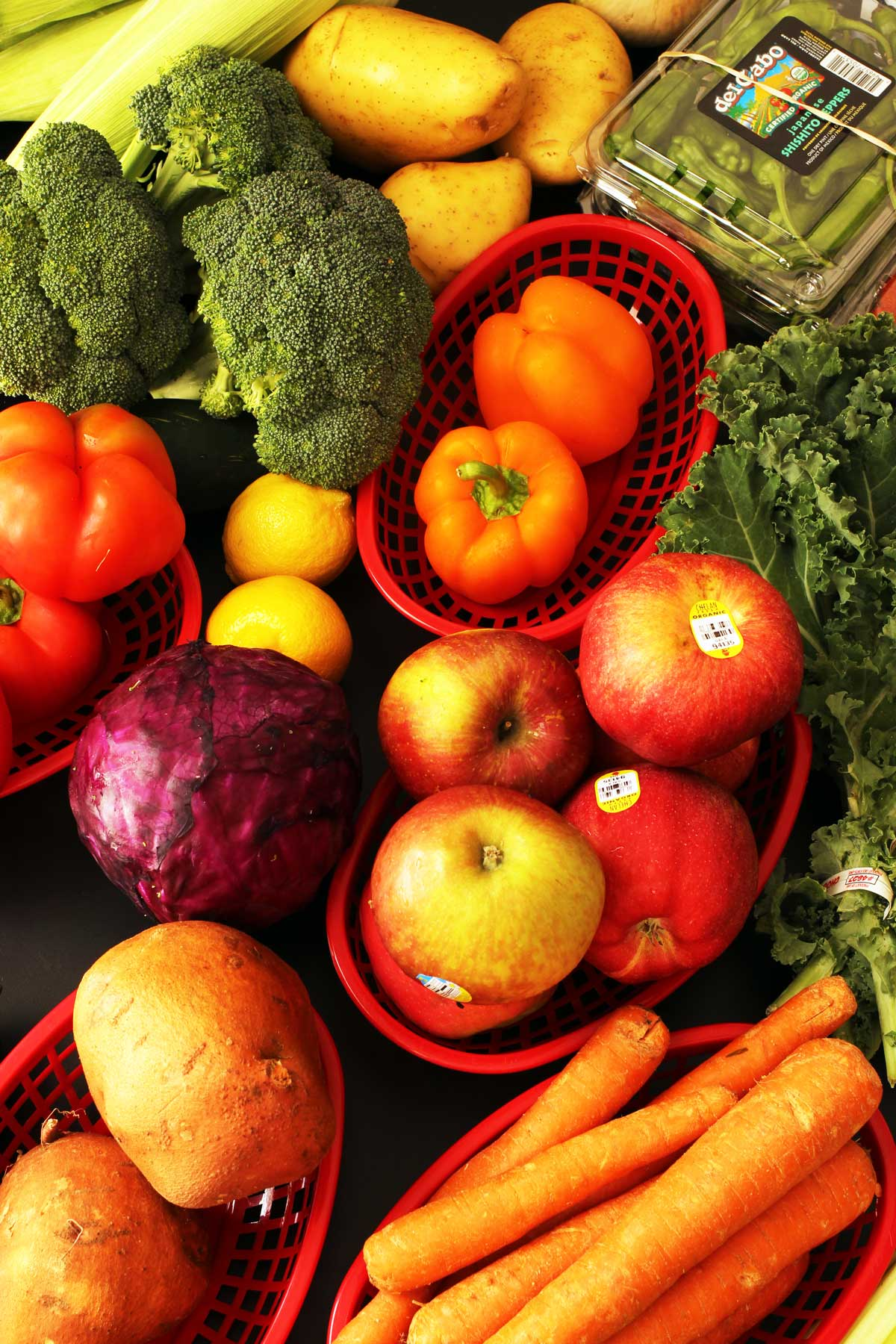 array of fruits and vegetables sorted into red plastic baskets.
