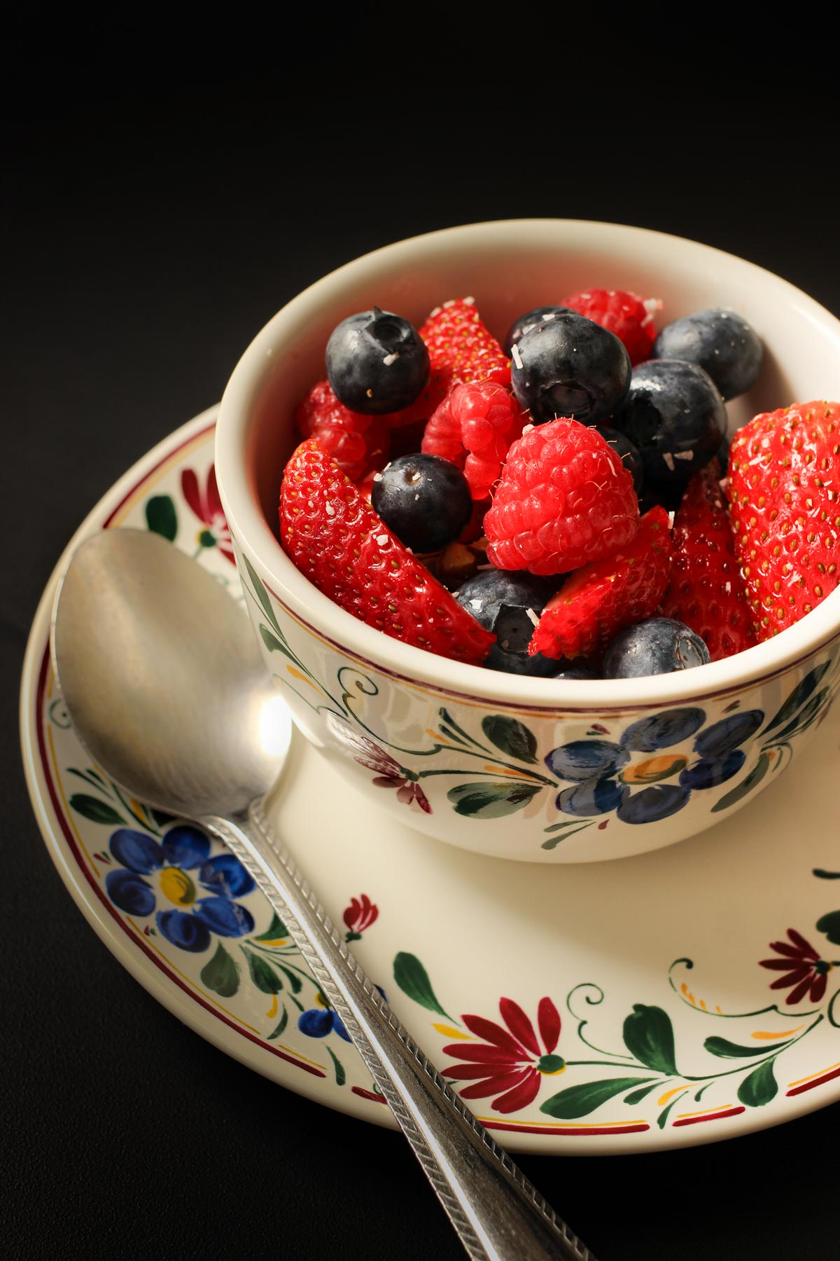 berry salad in a teacup with a spoon on the saucer.