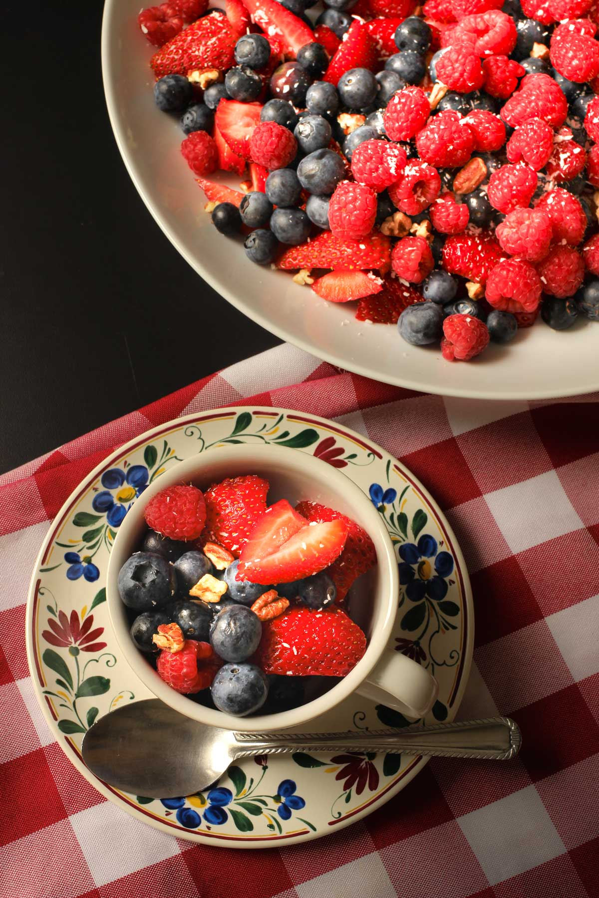 platter of berry salad near a floral teacup piled with berries.