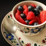 floral teacup loaded high with berry salad with spoon on saucer.