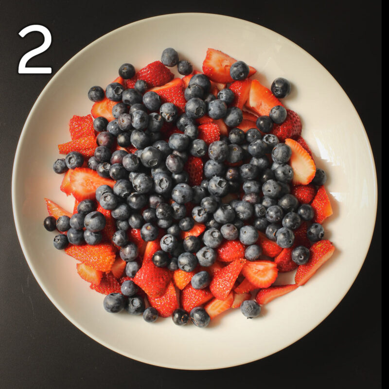adding blueberries atop the strawberries in serving platter.