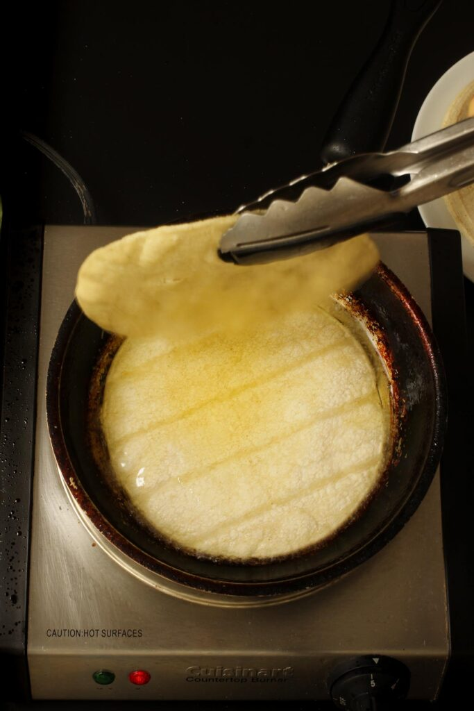 letting one tortilla drip oil back into the pan while the next one is frying.