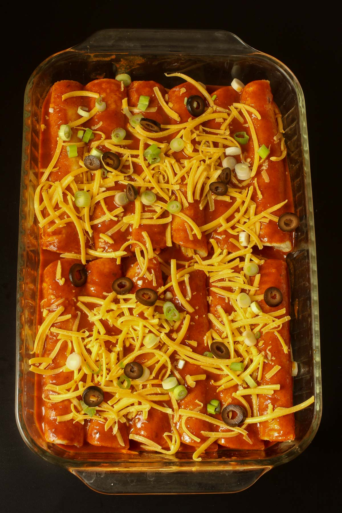 cheese enchiladas assembled in a large glass baking dish.