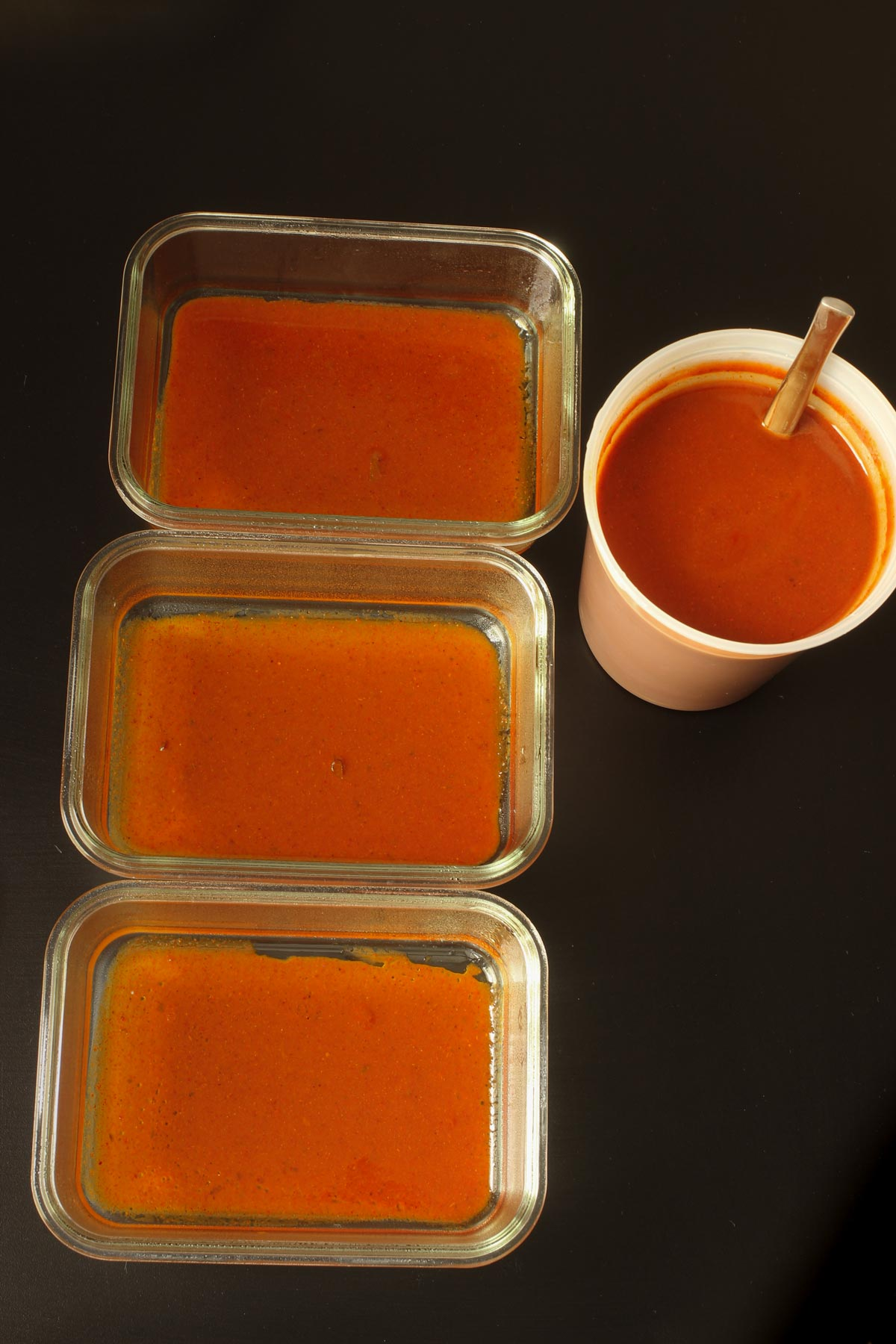 individual glass dishes with enchilada sauce spread across the bottoms.