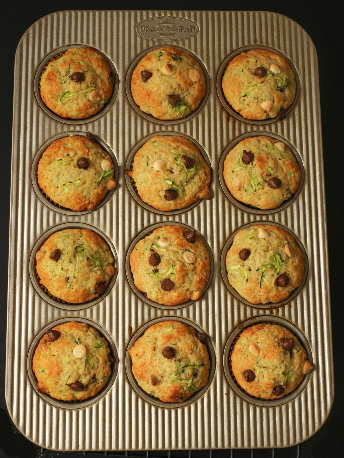 baked chocolate chip zucchini muffins in the muffin pan.