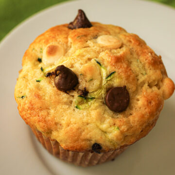 zucchini muffin with dark and white chocolate chips poking out the top.