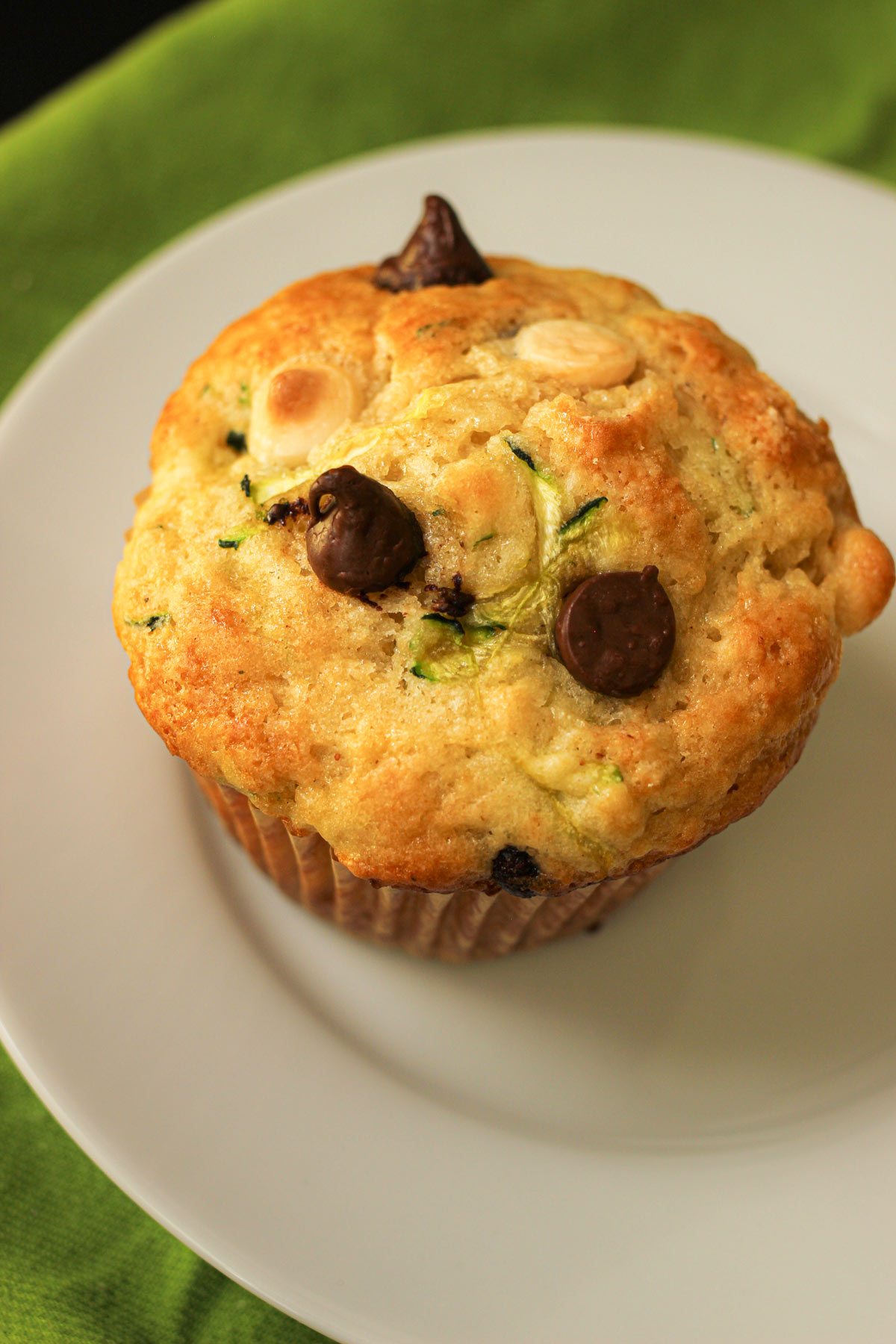 single chocolate chip zucchini muffin with chips poking out on a white dish near a green cloth.