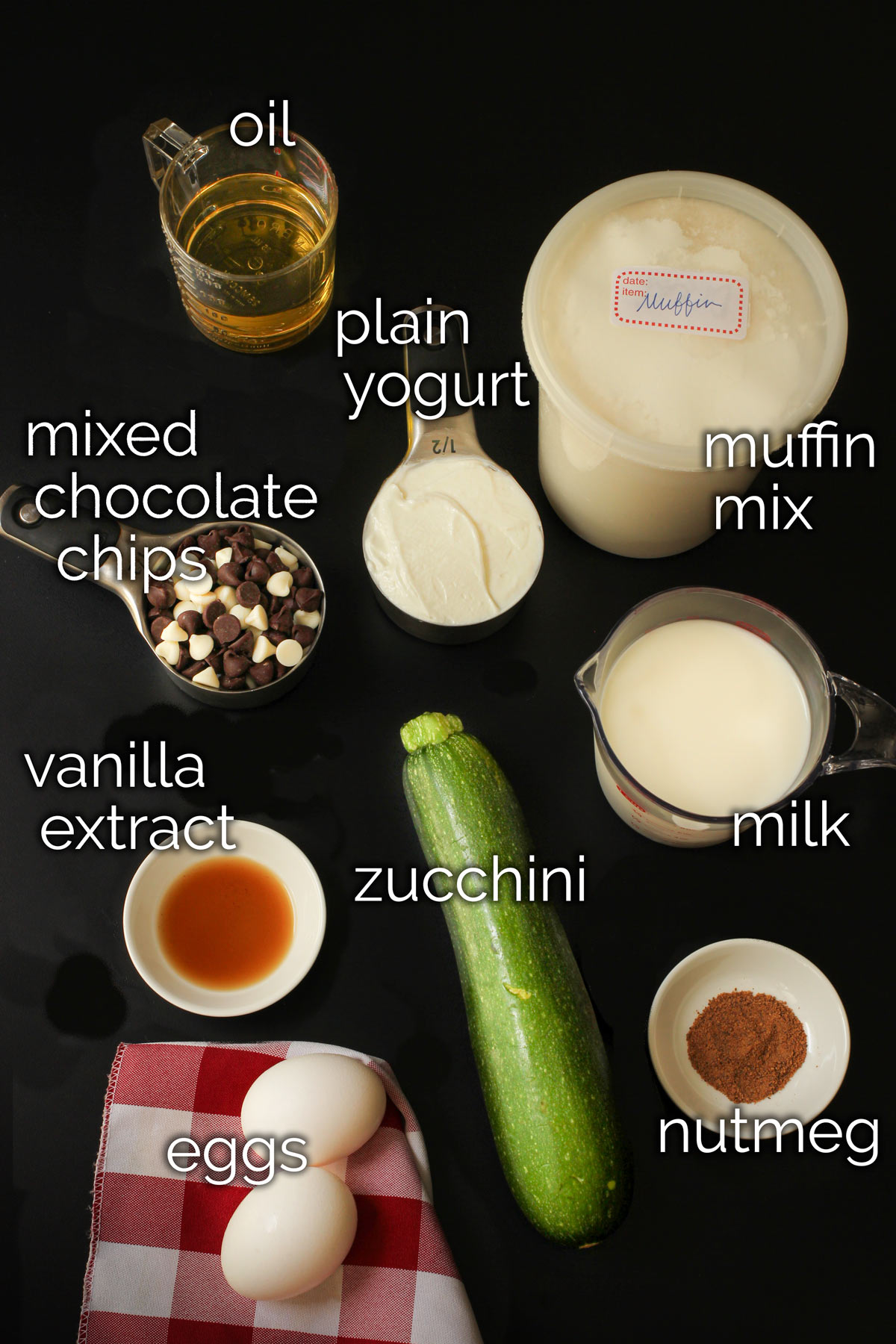 ingredients for chocolate chip zucchini muffins laid out on a black tabletop.