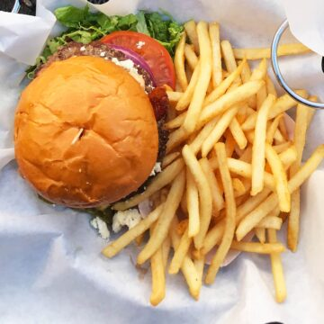 close-up of a deluxe burger in a basket with fries.