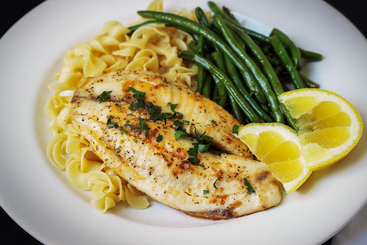 plate of cooked fish with garlic butter over a bed of egg noodles with green beans and lemon wedges.