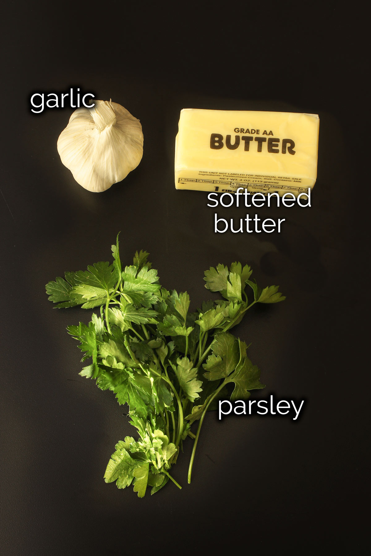 ingredients for garlic butter laid out on a black table.