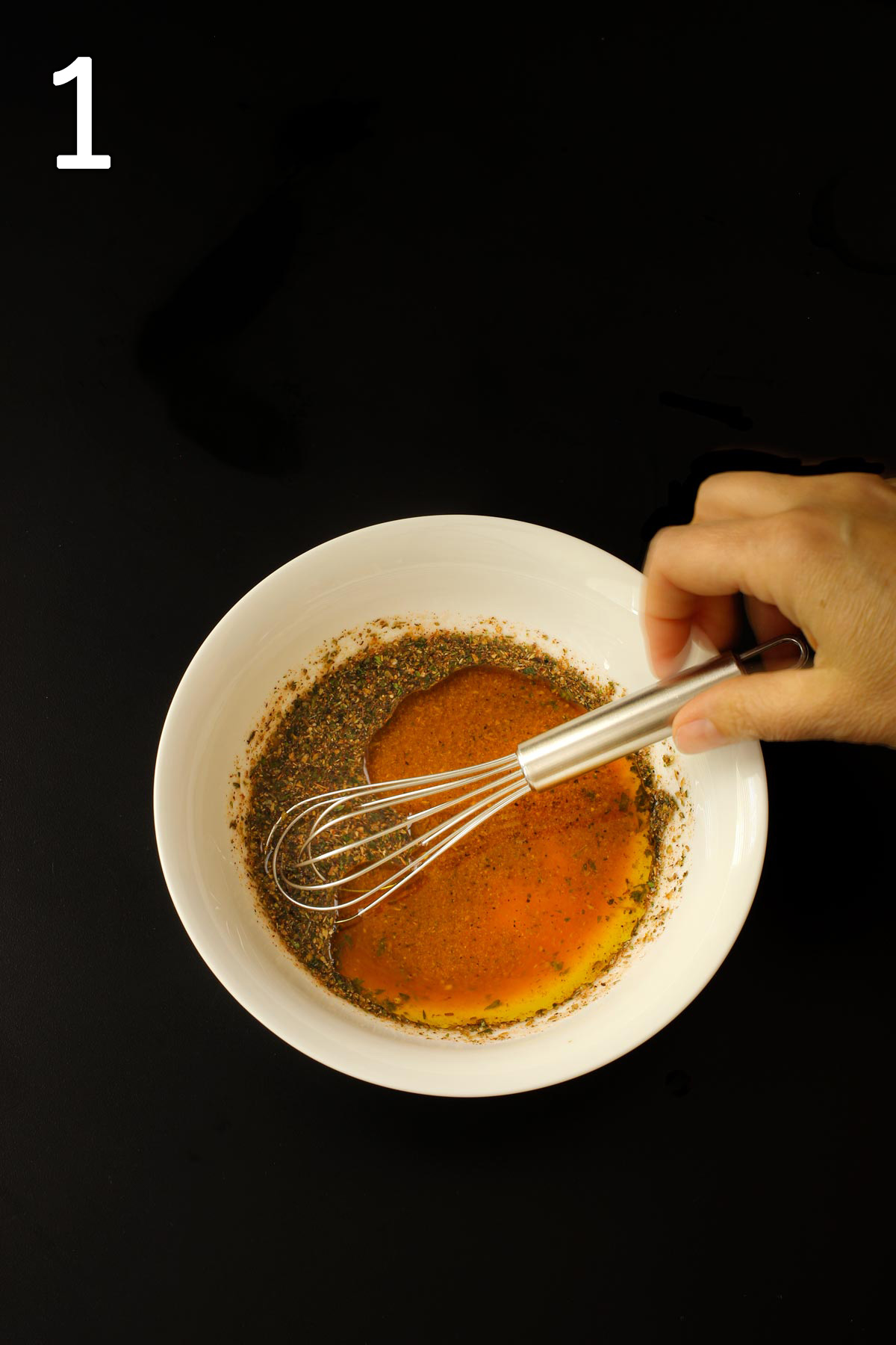 greek marinade ingredients in white bowl, hand holding whisk.