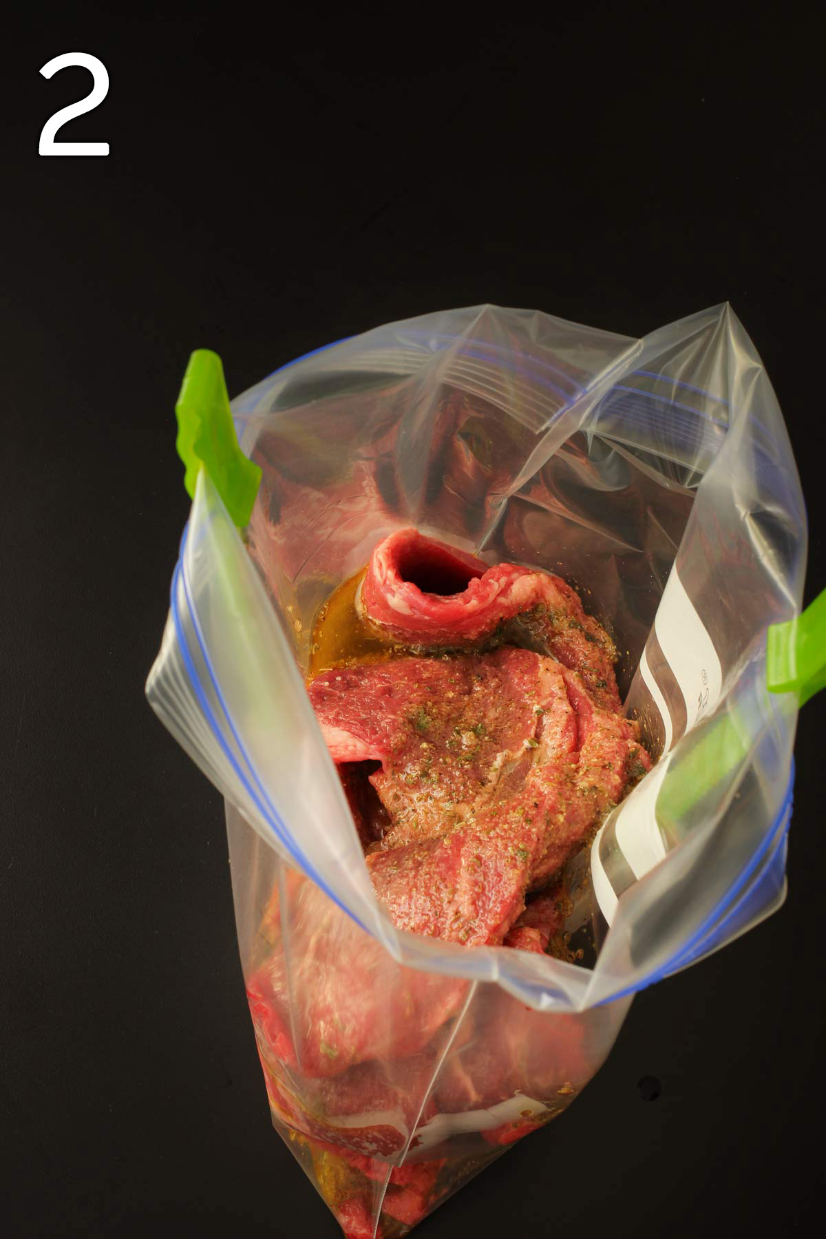 steak in freezer bag with greek marinade poured over it.
