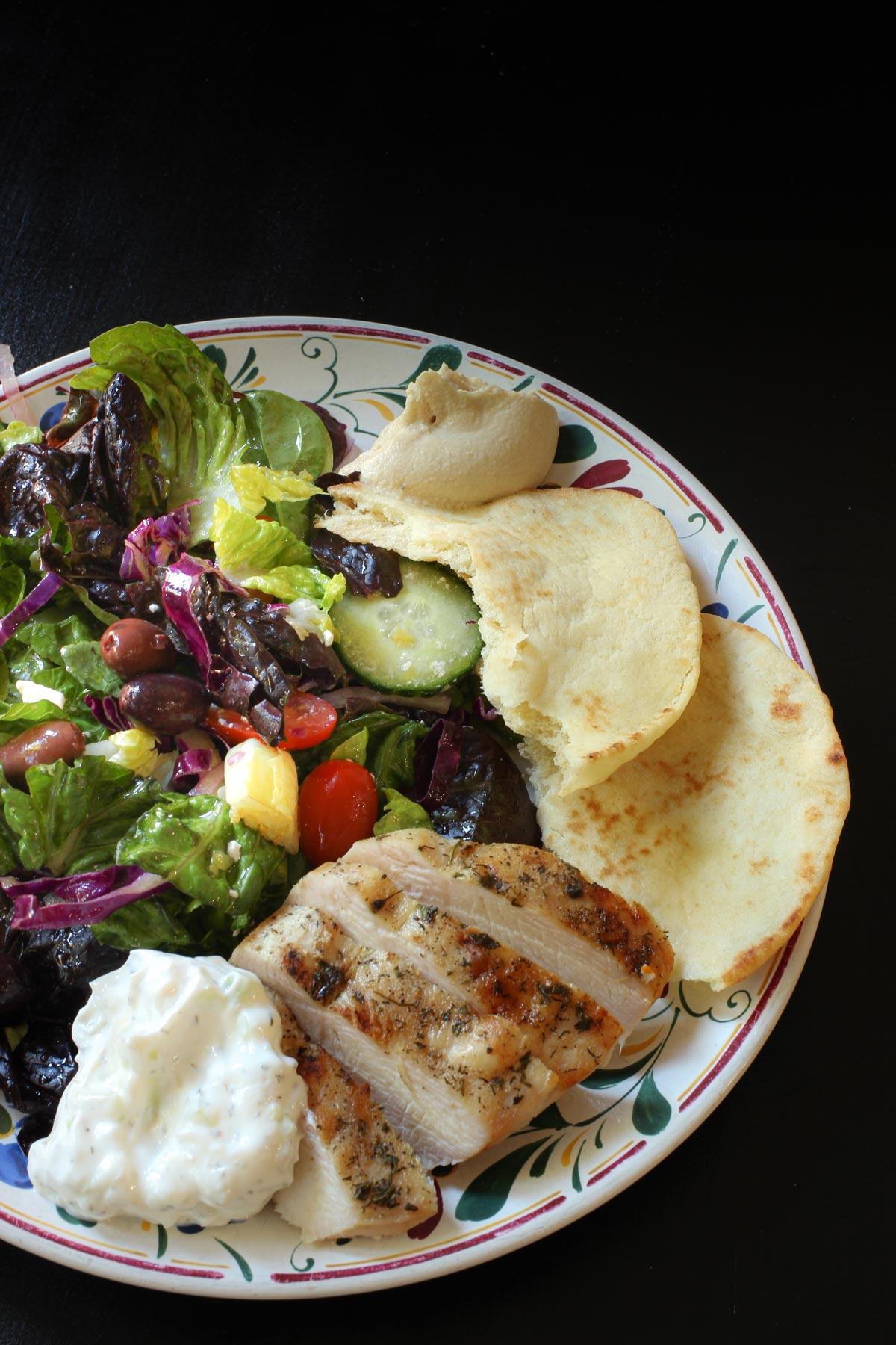 greek meal of grilled chicken with Greek seasoning, pita, salad, and tzatziki.