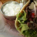 metal cup of garlic yogurt sauce next to greek pita sandwich in lined basket.
