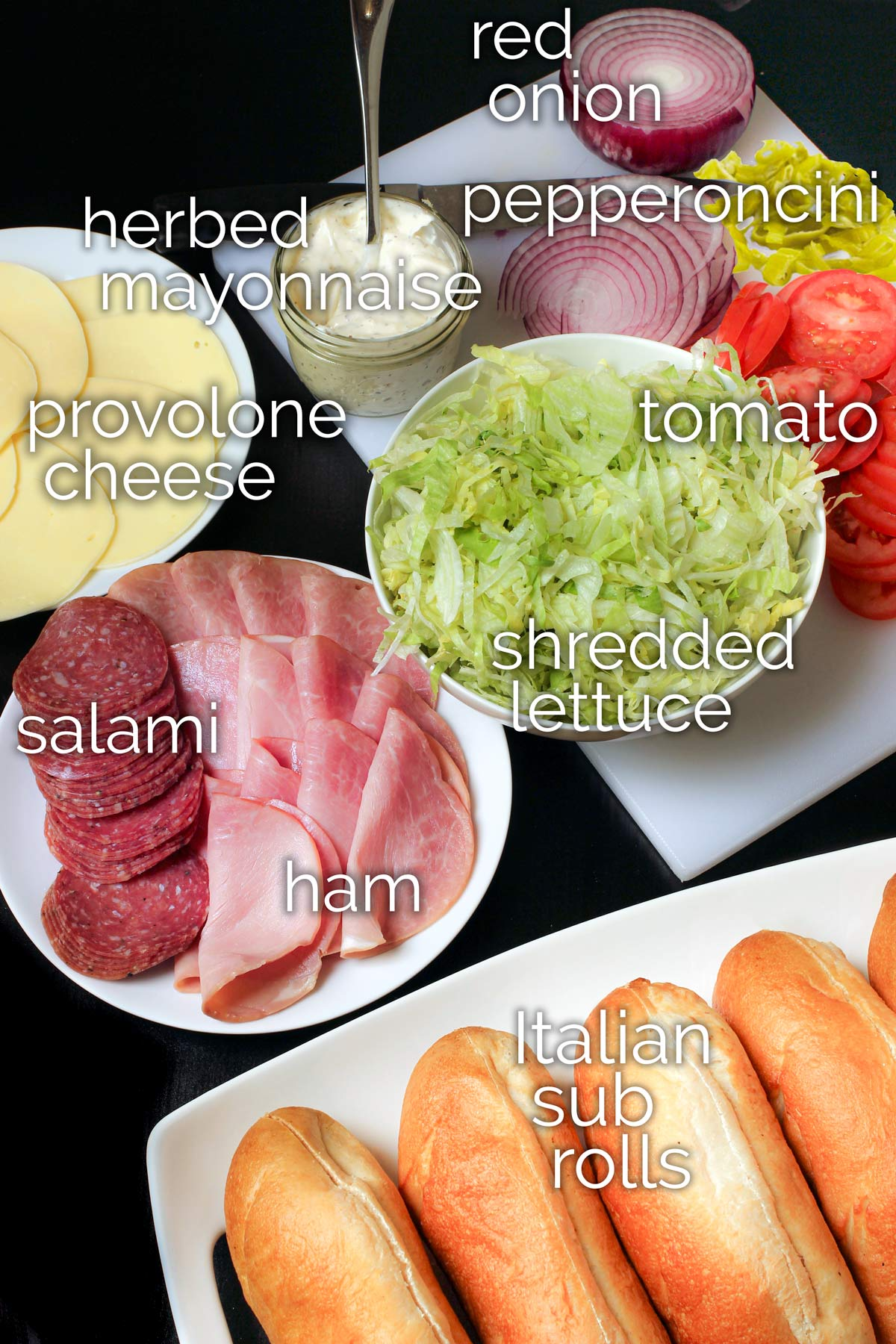 Italian cold cuts with plate of cheese and platter of vegetables next to sub rolls.