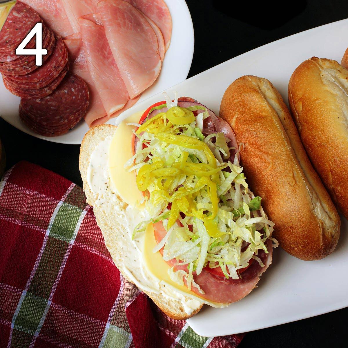 lettuce, tomato, onion, and pepperoncini layered into Italian sub sandwich.