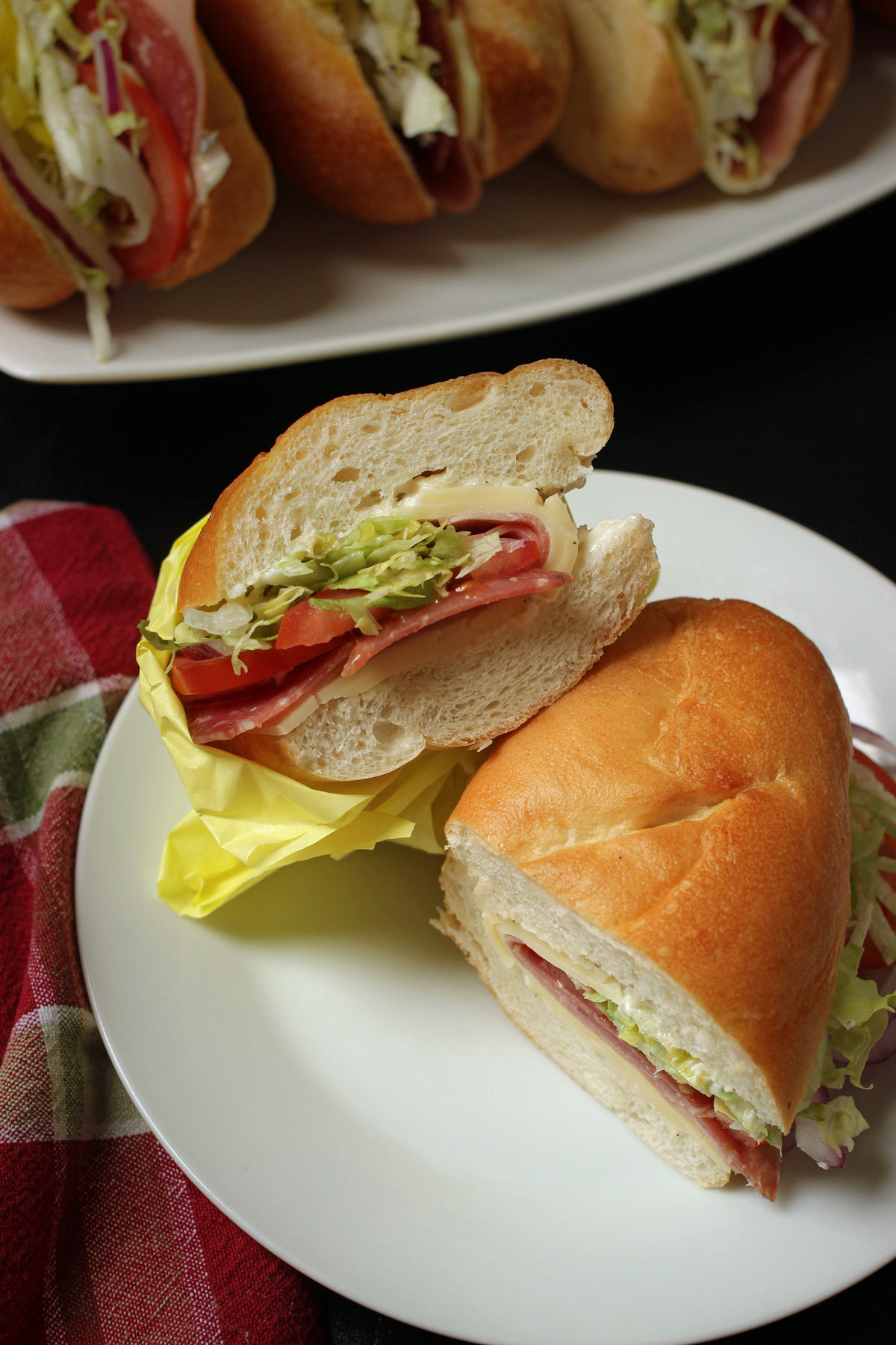 Italian sub sandwich cut open and two halves on a plate.