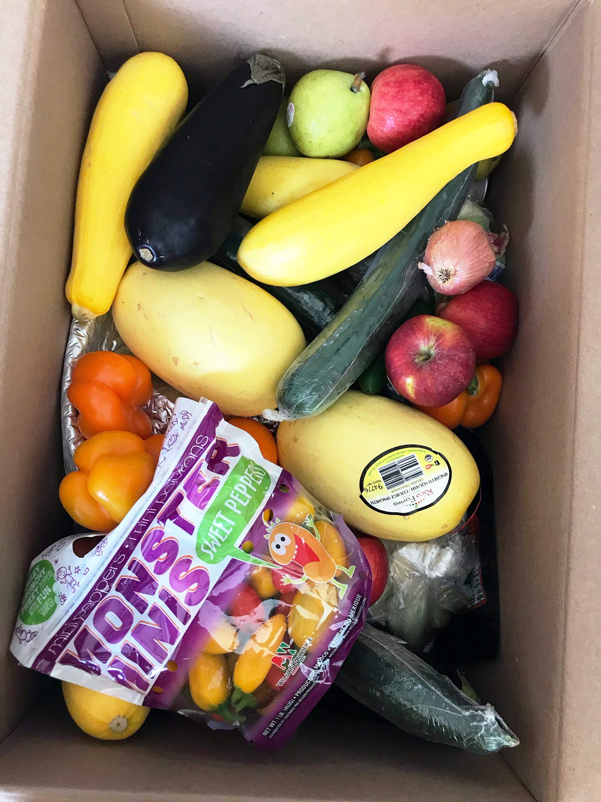 cardboard box full of a mix of fruits and vegetables.