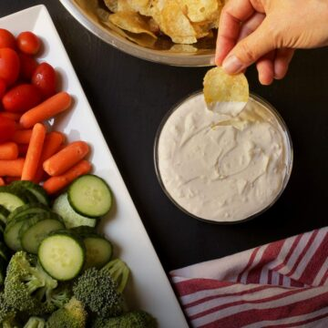 hand dipping a potato chip into bowl of sour cream onion dip near platter of veggie dippers.