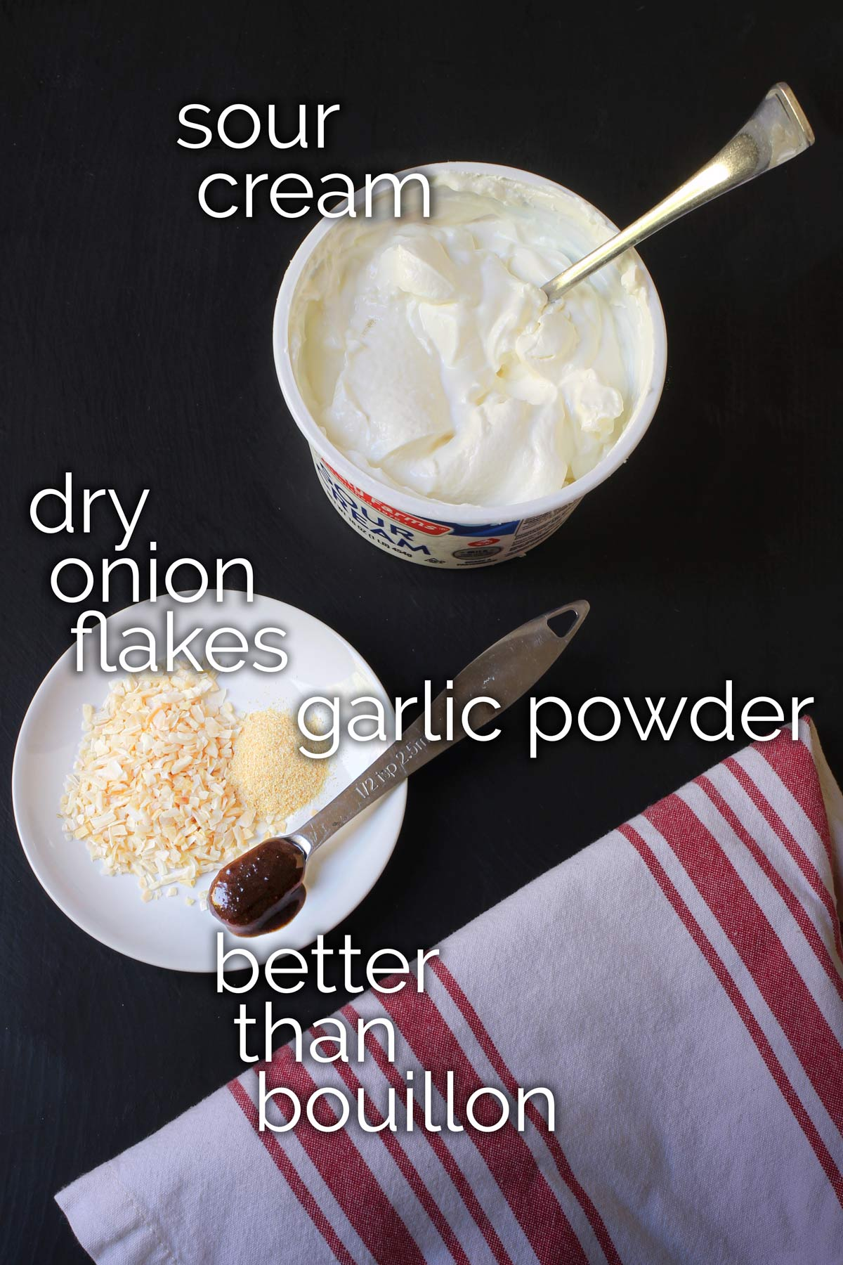 sour cream, onion flakes, garlic powder, and bouillon measured out on table top.