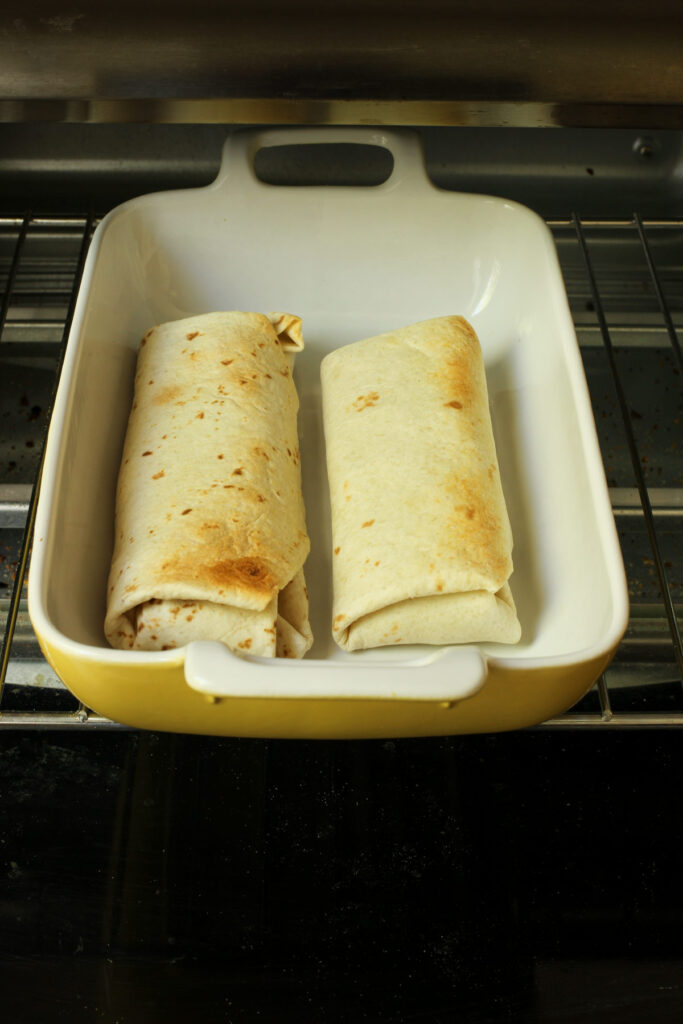 two burritos baked in a yellow baking dish.