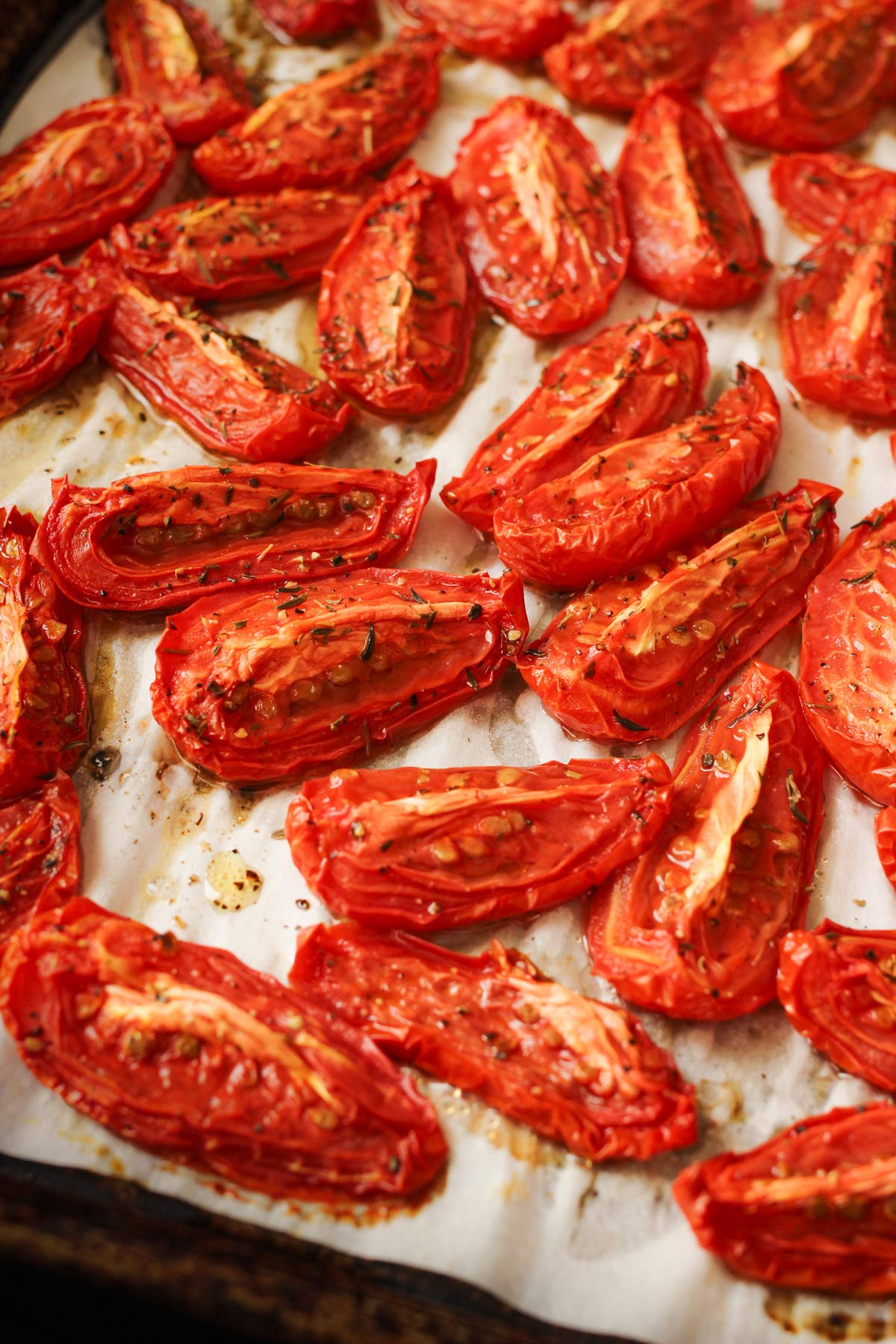 oven roasted tomatoes scattered on parchment on a sheet pan.
