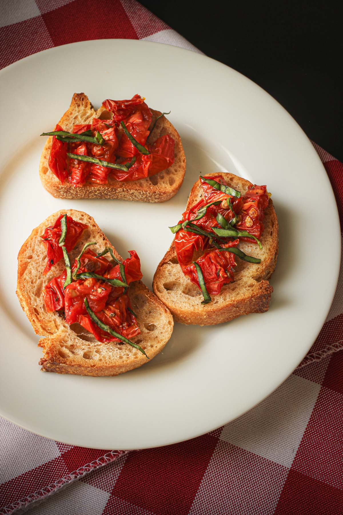 plate of toasts topped with oven roasted tomatoes with basil chiffonade.