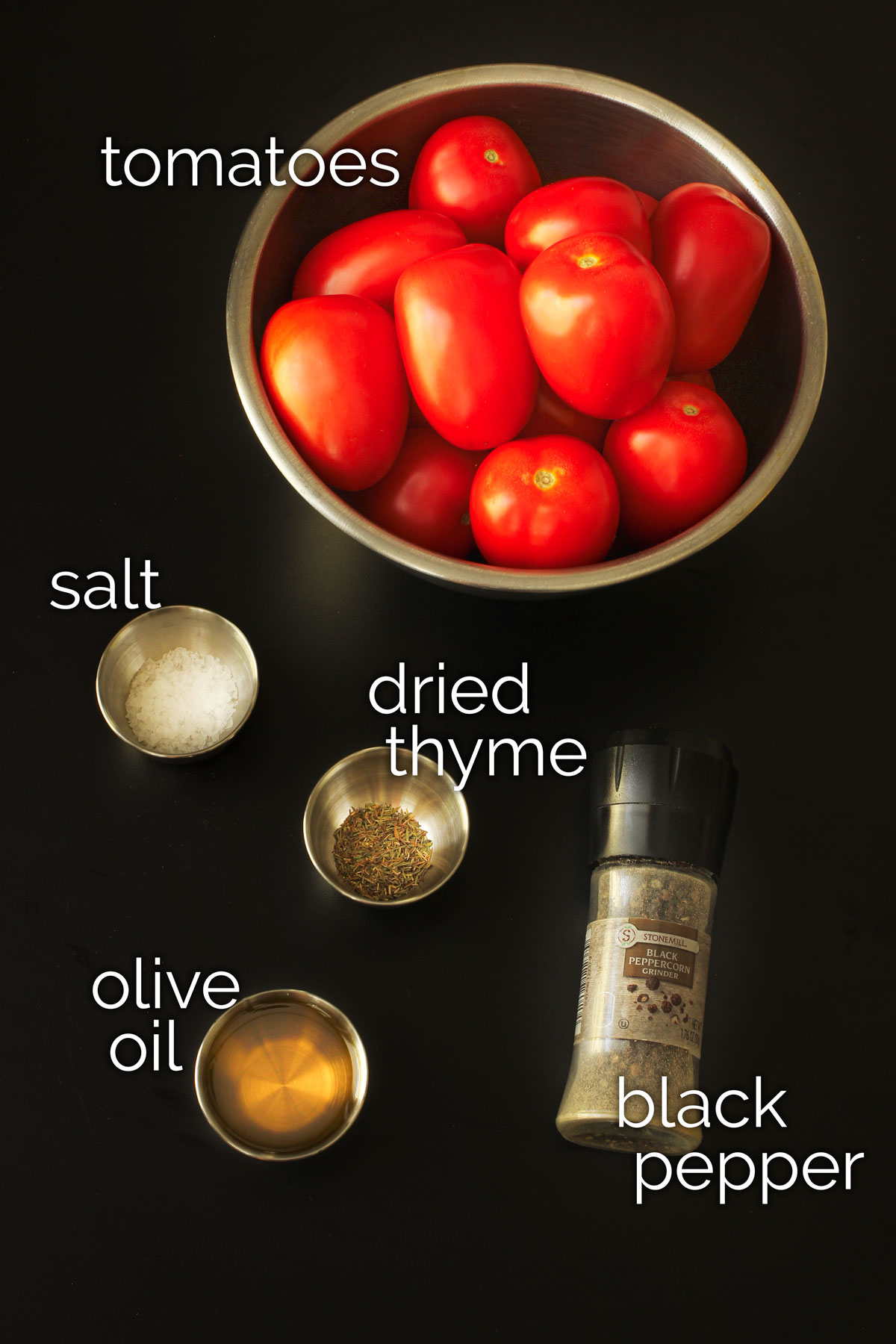 ingredients for roasting tomatoes in the oven laid out on black tabletop.