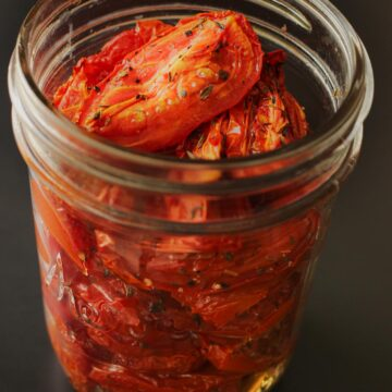 oven roasted tomatoes piled in a mason jar.