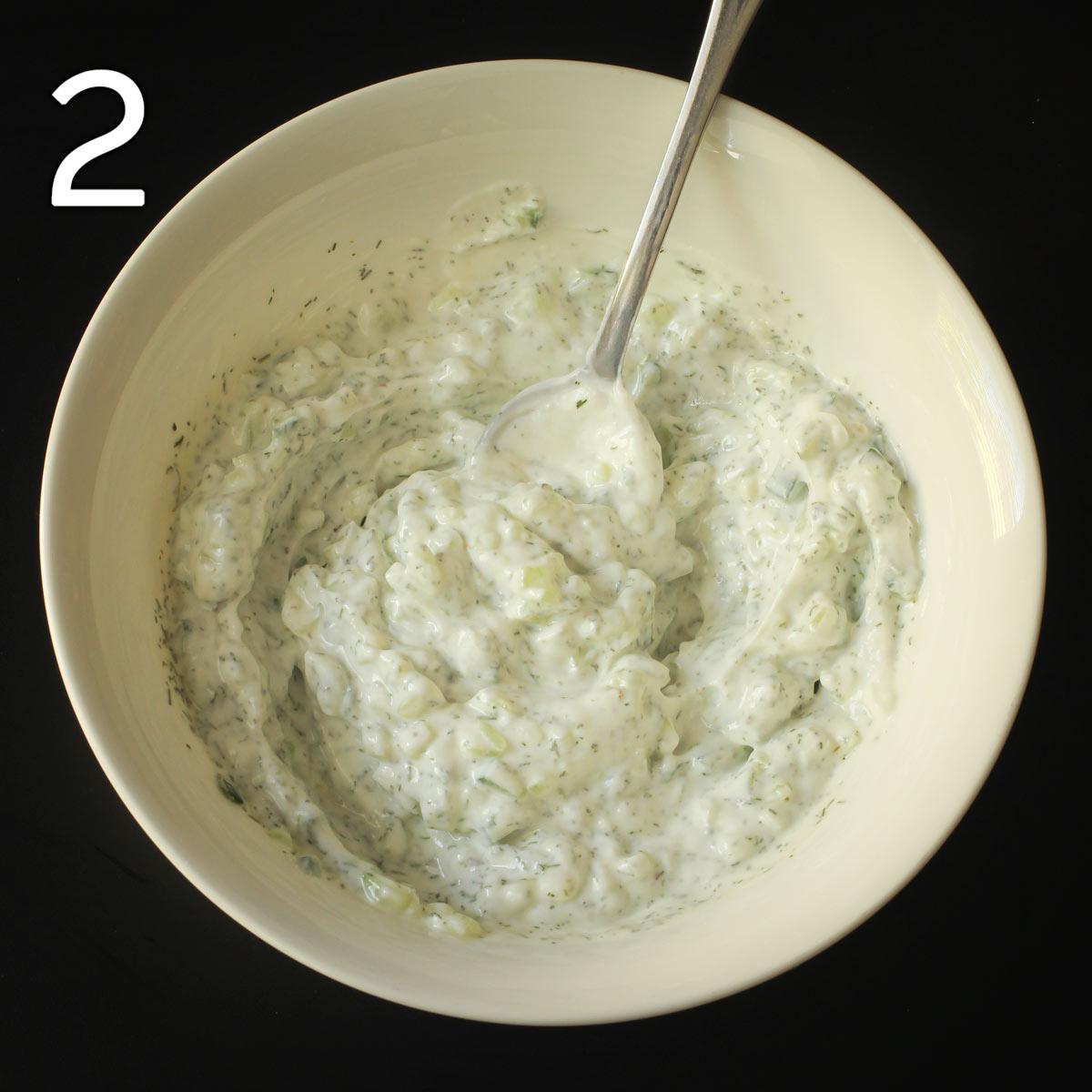 a white bowl full of garlic yogurt dip.