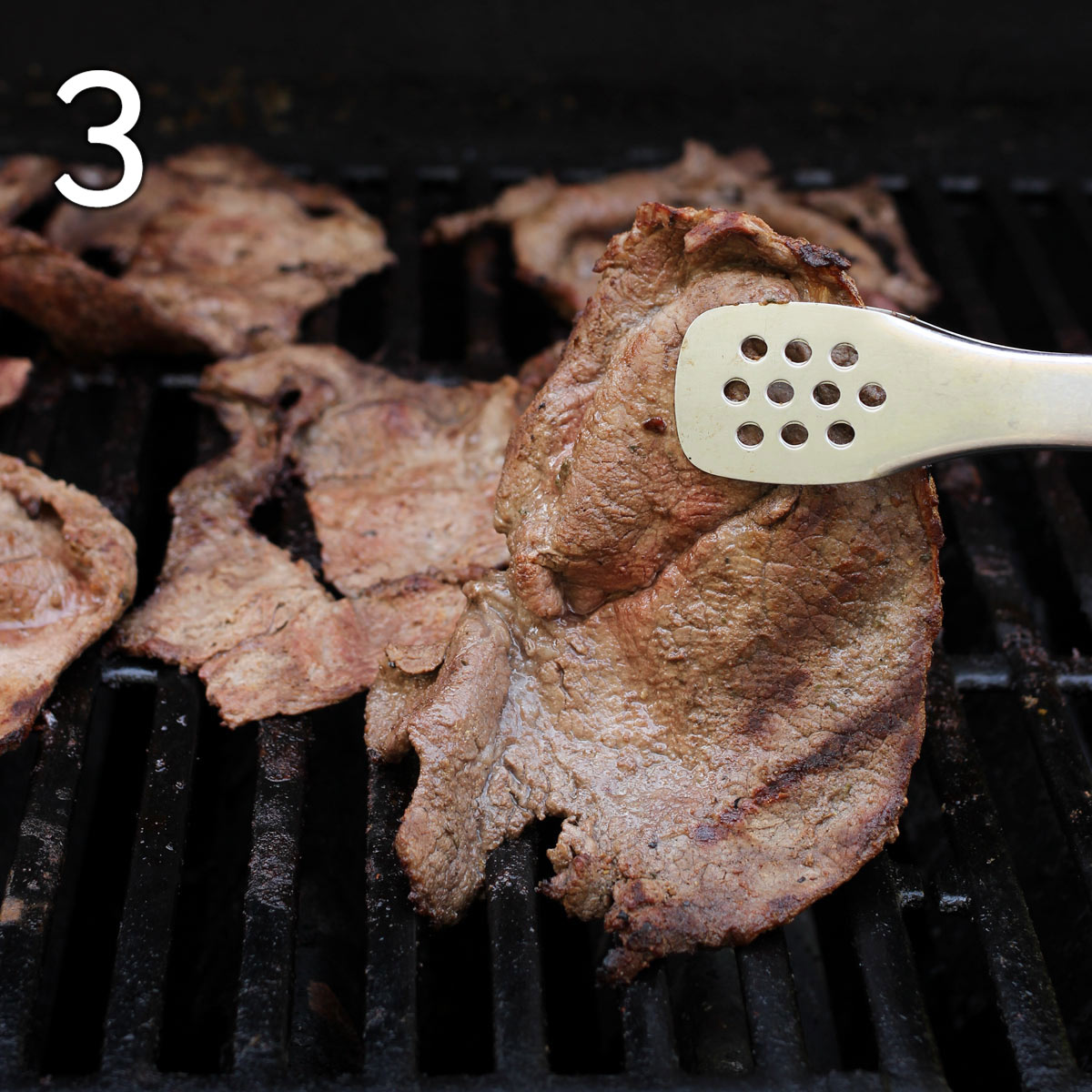 tongs lifting grilled steak from a hot grill.