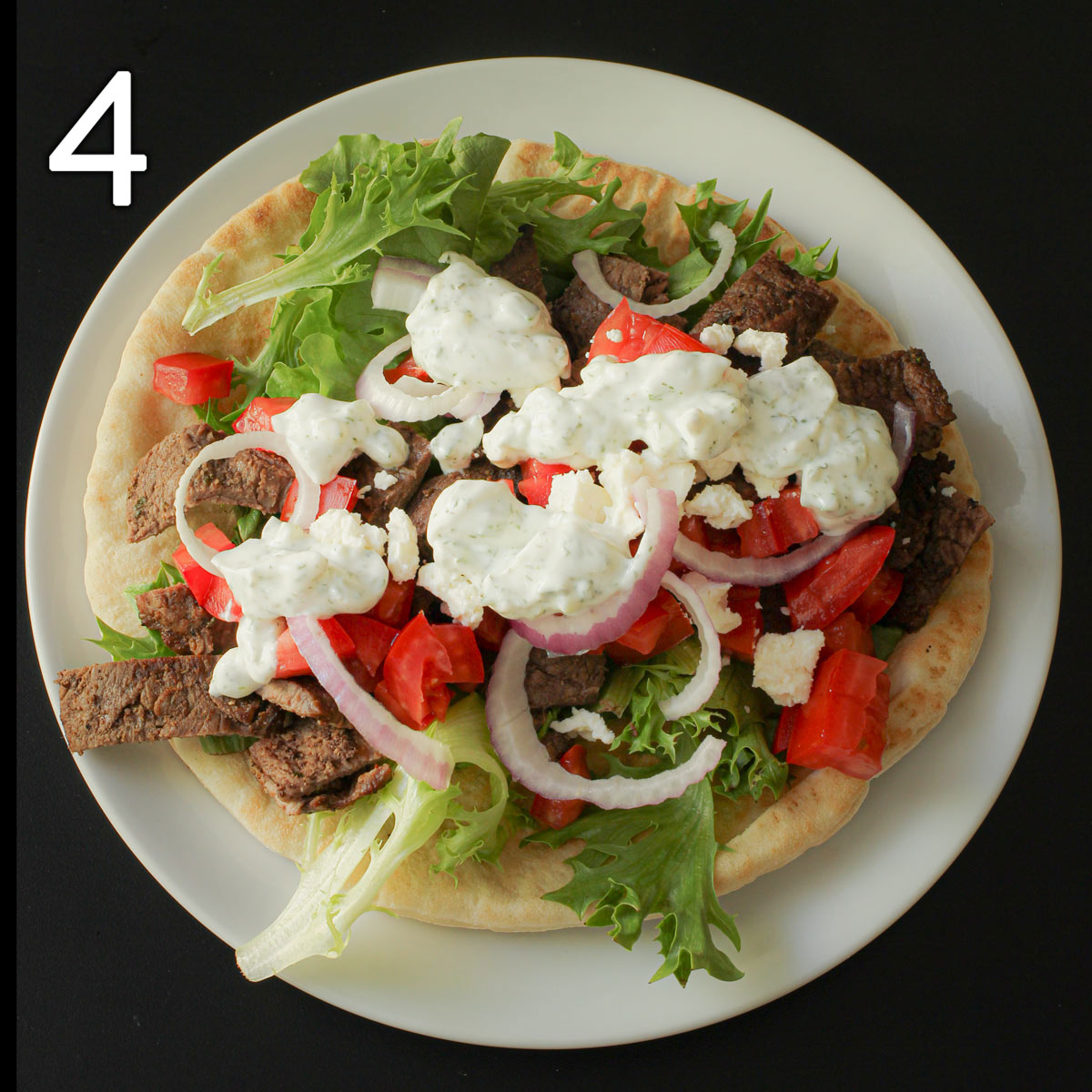 a pita round piled with steak, vegetables, feta, and tzatziki sauce.